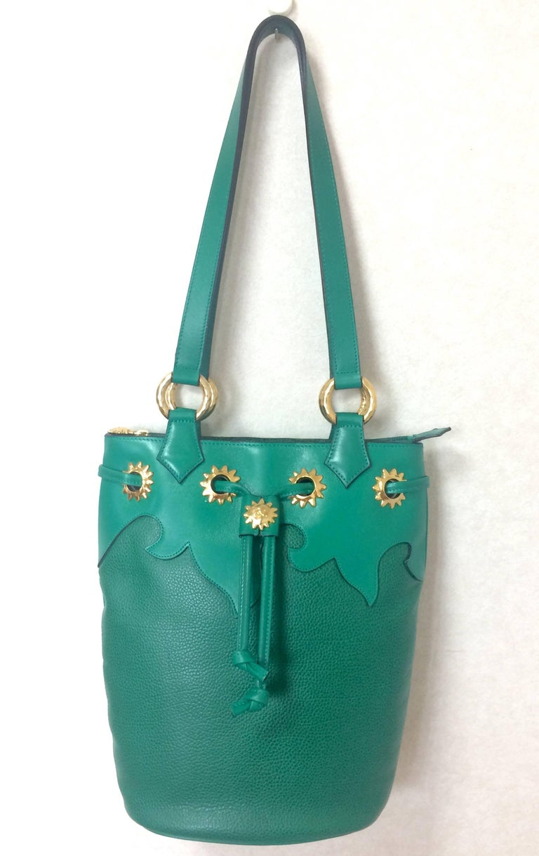 1990s. Vintage Christian Lacroix genuine grained green leather hobo bucket shoulder bag with golden sun motifs.  Hot masterpiece.  This is a Christian Lacroix green grained leather hobo bucket style shoulder bag with gorgeous golden sun motifs round