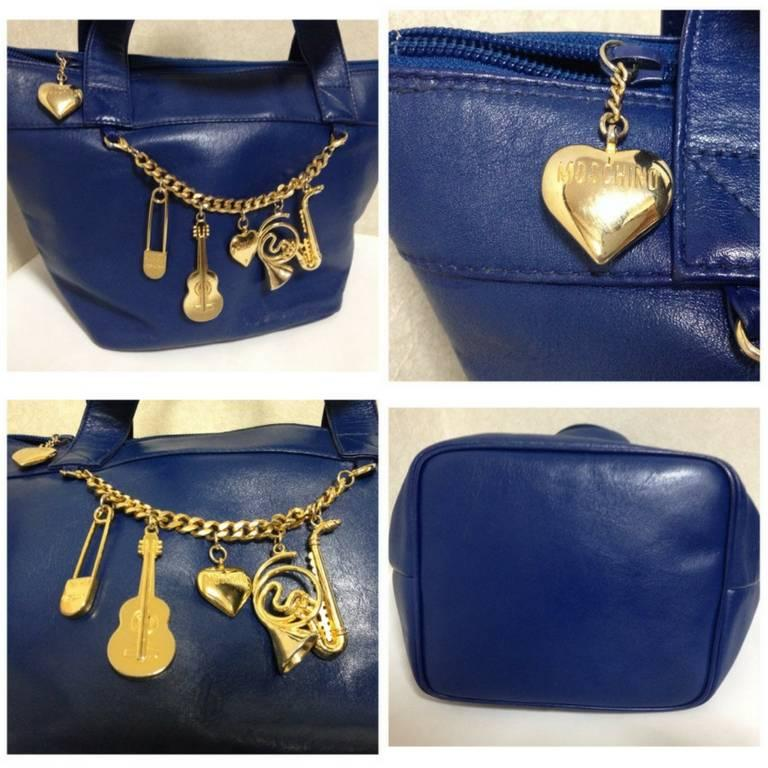 1990s. Vintage Moschino navy blue leather classic tote bag with golden cute dangling charms. Masterpiece jewel bag.  Introducing a chic and cute vintage piece from Moschino back in the early 90's! Featuring cutest golden charms of heart, guitar,