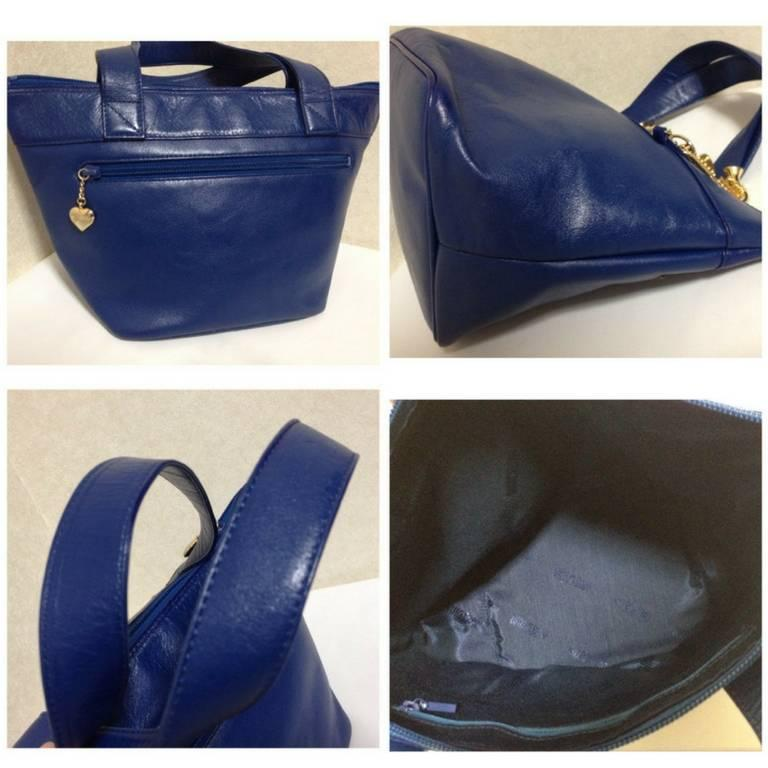 Blue Vintage Moschino navy blue leather classic tote bag with golden dangling charm. For Sale