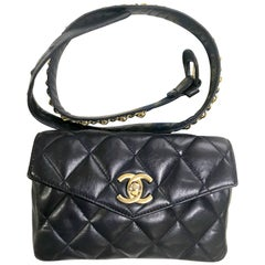Vintage CHANEL dark navy lamb leather waist bag, fanny pack with golden chains.