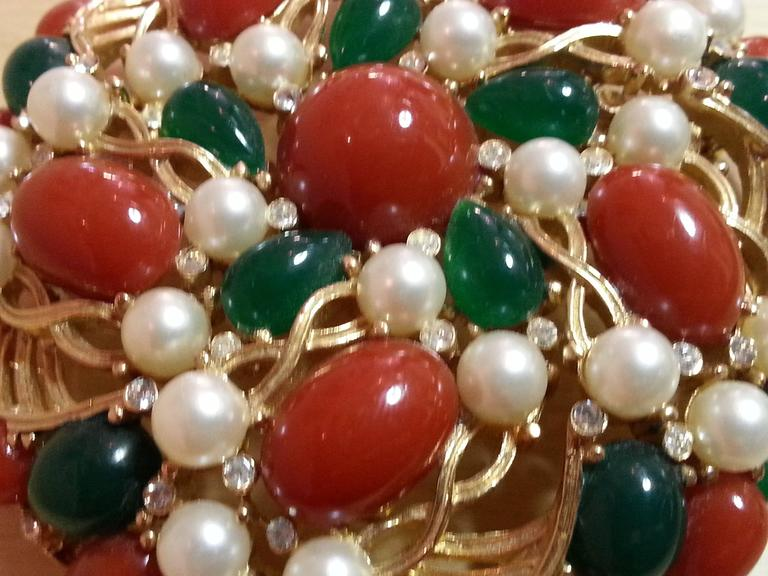This large brushed goldtone TRIFARI pin dates from the 1960's and incorporates classic aspects of Mogul designed jewelry design in its period format. Flat backed faux emerald and coral cabochons provide rich color and texture in contrast to the