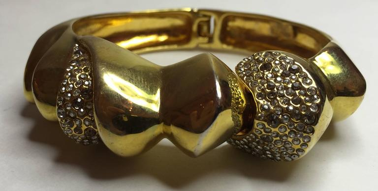 While Alexis Bittar is known as a contemporary master working in acrylic medium, he also works in standard metalsmithing materials. This 21st Century Alexis Bittar Unusual Goldtone Hinged Bracelet is encrusted with alternating sections of high
