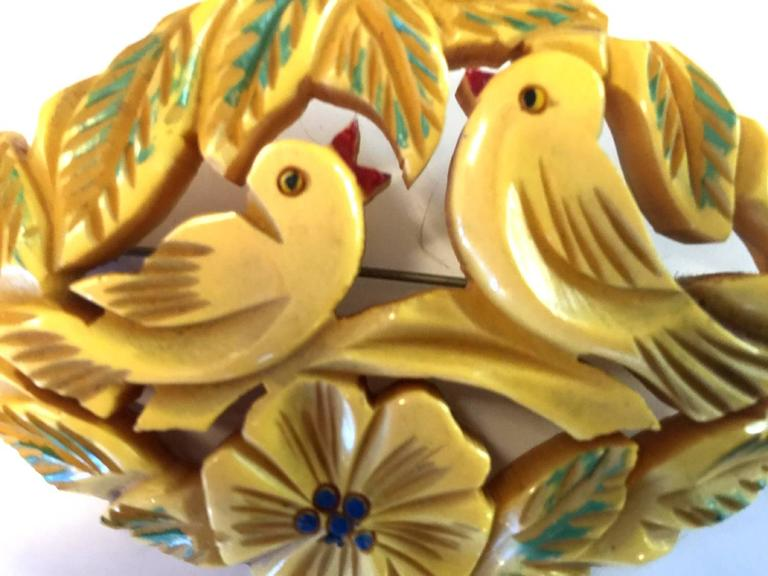 A heavily carved bone bakelite brooch depicts adorable love birds in silhouette beak to beak chirping poses. Surounded by flowers and naturalistic details, the pin has a by hand artisan painted detailing which adds much color and whimsy to the