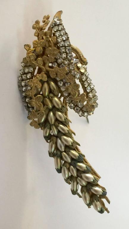 Among the loveliest pearl and goldtone Miriam Haskell brooch pins ever, this floral figural delphinium brooch makes a figural statement ..large ,elongated and detailed--just like the exquisite tall form of the delphinium blossom.  Most floral shapes