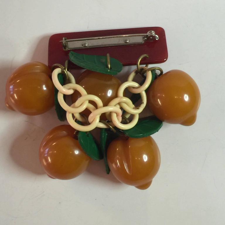 This classic art deco 1930s bakelite fruit pin is a rarity. Cherries are the most common....with most other fruits being much rarer. Apricots, particularly rare. A resin washed rectangular barpin  is carved and colored to ressemble tree bark, and 5
