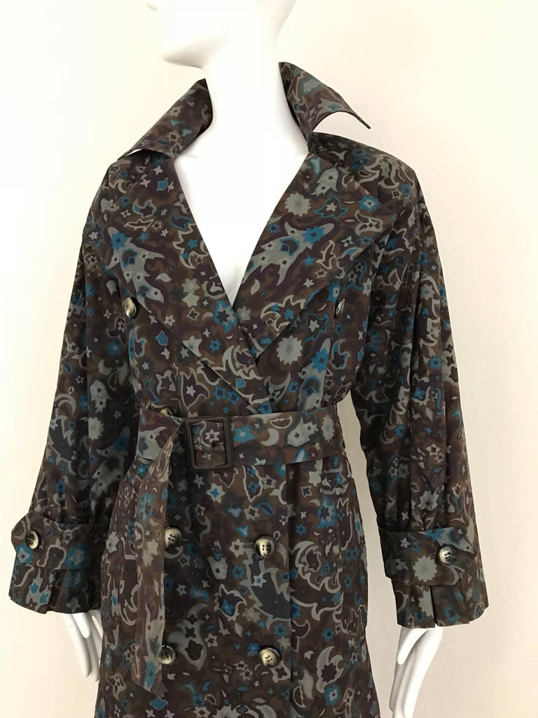 This vintage trench coat by Yves Saint Laurent has the classic good looks we expect from the cut of a trench coat, but the paisley print made of  teal blue and gray, set on a light muted brown background creates a unique look.  This trench would