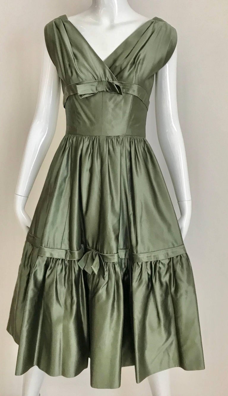 Classic 1950s Christian Dior Boutique - New York Cocktail Dress. Beautiful moss green silk satine V neck dress with bows and cap sleeves. Dress has thin crinoline underneath.    Fit size US 2/4 ) See Measurement: Bust: 32 inches/ Waist: 24 inches