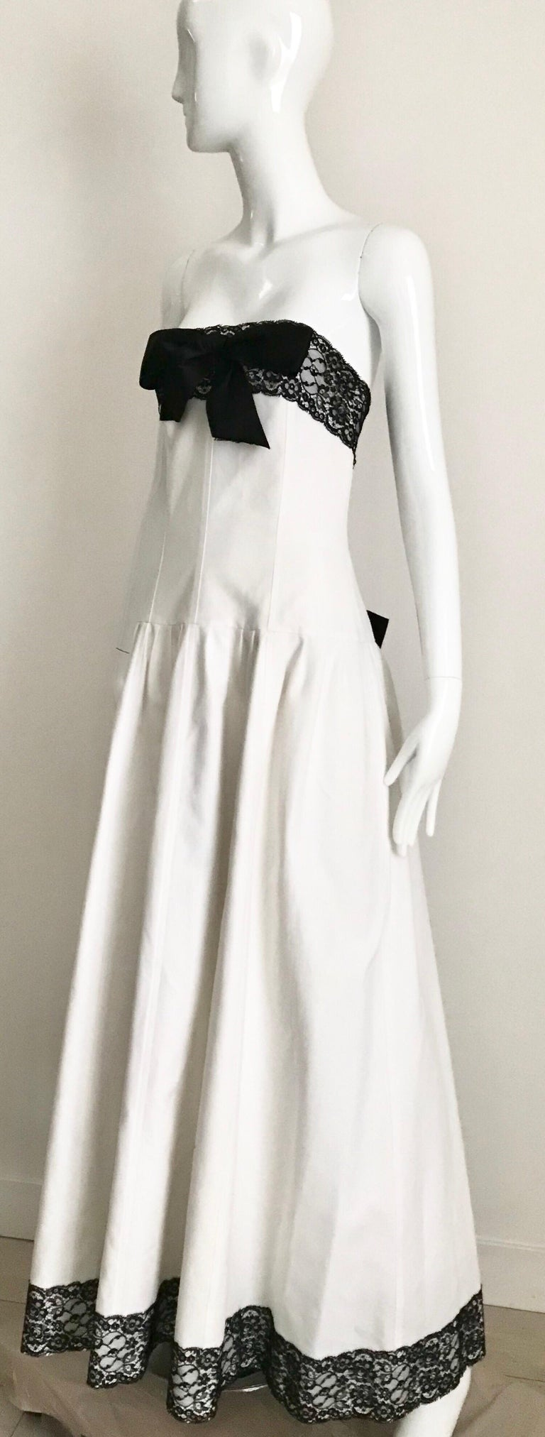Timeless Vintage Chanel white cotton piquè strapless gown with black lace ribbon trimming. Slightly drop waist. Corset underneath. Fit: XS/SM (2-4) Bust:32 inches/ Waist: 25 inches *This garment  has been professionally dry cleaned
