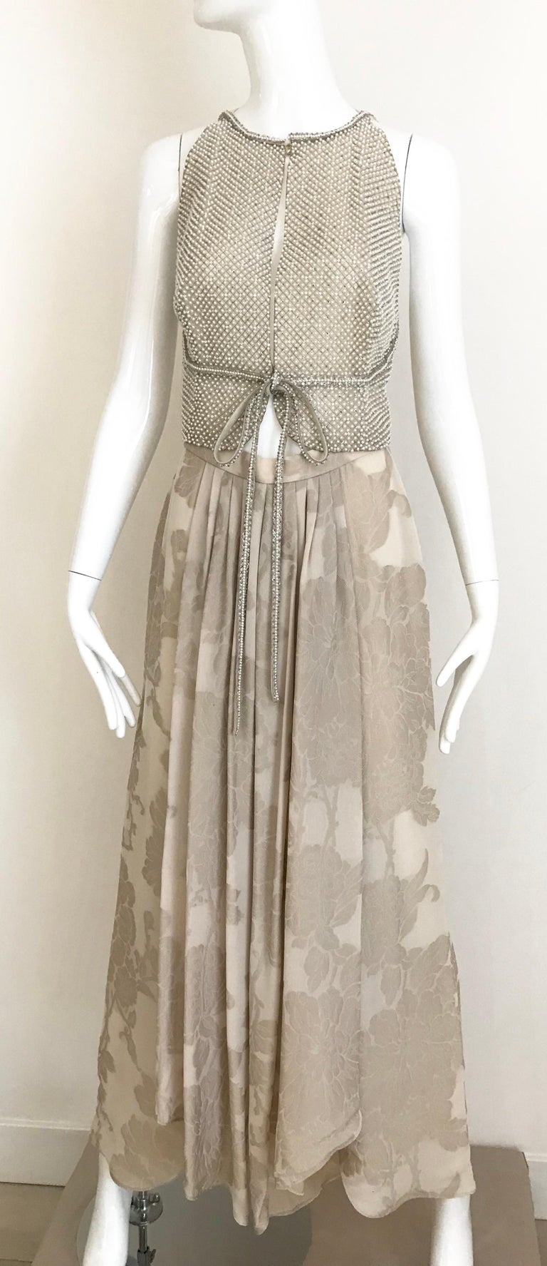 Incredible Giorgio Armani 3 pcs Creme beaded vest top, heavy crystal encrusted top and beautiful Creme silk jacquard pants. Pants measurement: Waist: 26 inches/ Hip: 38 inches/ Pants length: 44 inches Pearl Vest: Bust: 32 inches/ Top length: 18