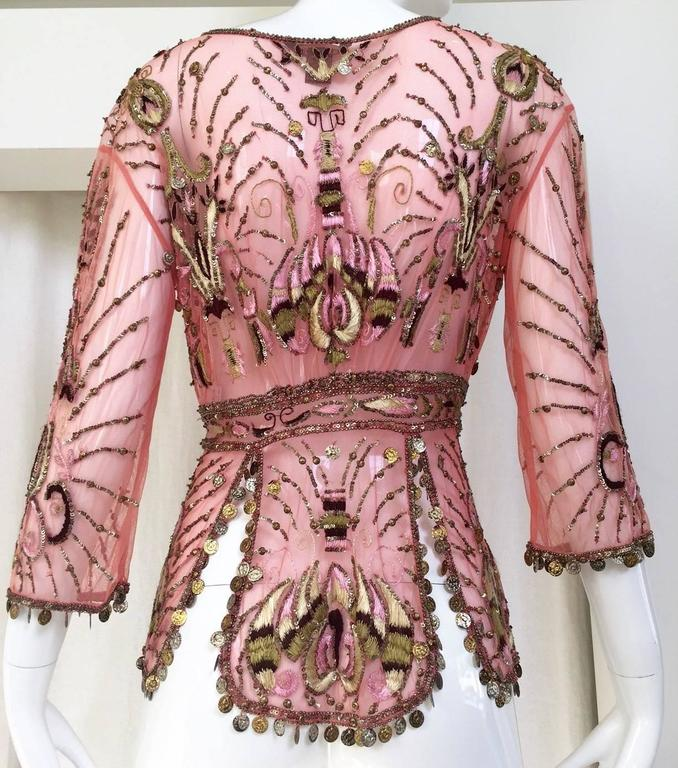 Beautiful Roberto Cavalli embroidered mesh beaded silk cardigan in salmon pink. Three quarter length sleeves. cardigan/blouse has tie closure. gold charms on the sleeves and at the bottom trim of the blouse.