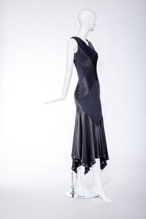 "This 1990's John Galliano black silk charmeuse dress has a biased cut and is inspired by a 1930's design. The hemline is studded with silver grommets and there is a subdued ""X"" pattern on the front and back of the dress and the draping of the cowl"