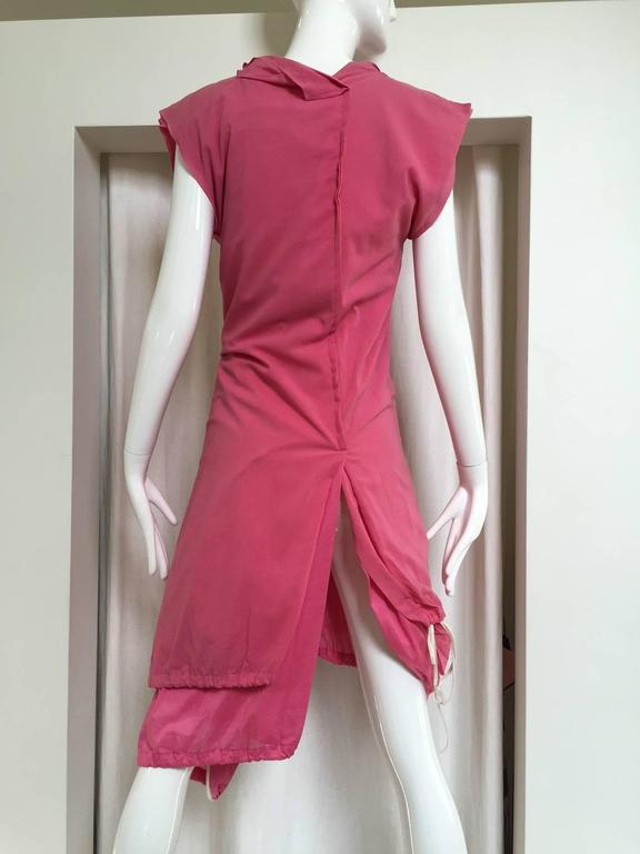 2007 Comme Des Garcons buble gum pink cotton double layer shirt dress with drawstring. two different double layer shirt dresses in two slightly different pink fabrics are joined down the rear center seam, each layer buttons up down the