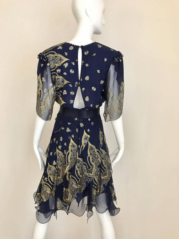 This 1980s blue Zandra Rhodes silk chiffon cocktail dress is highlighted with a gold and silver Indian print etched with sequins. The collar, shoulders and sleeve cuffs are edged with small pearls. The lower portion of the dress has a multi-layered