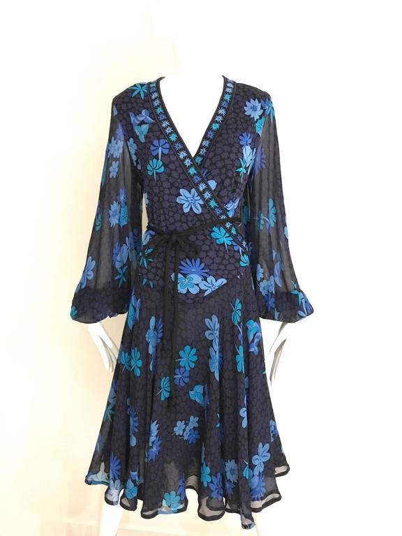 Vintage 1970s Bessi black light jersey dress in light blue florla print V neck dress with billowy sleeves. Dress is lined in silk and comes with black jersey cord belt. Large Size
