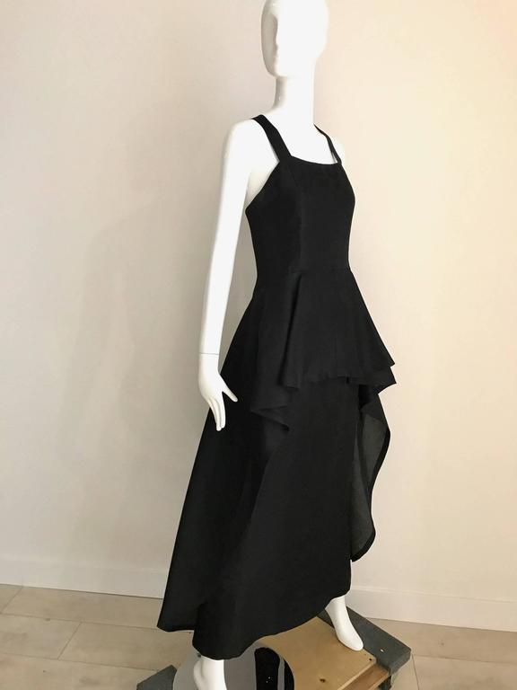 Timeless and chic Vintage Givenchy black silk organza gown with cris cross back and slightly cascading peplum hem. This vintage Givenchy gown is a signature look epitomized Audrey Hepburn classically chic style. Bust: 32 inch Waist: 27 inch Hip: 39