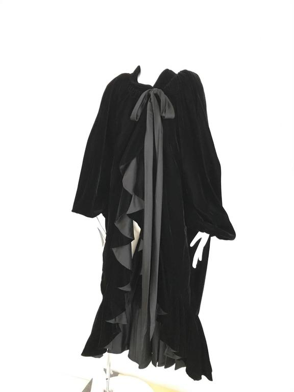 This rare 1980's Yves Saint Laurent black velvet evening coat /cape is the epitome of old world elegance. The design incorporates mild shoulder pads and large billowy sleeves that create the illusion of a cape. There is a very long, thin satin sash