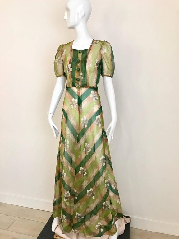 1930s Art deco print silk organza dress in green, tan, white and grey floral and chevron print. 4 lucite snap on front button  and zip on the side.  Size: 4/6 small