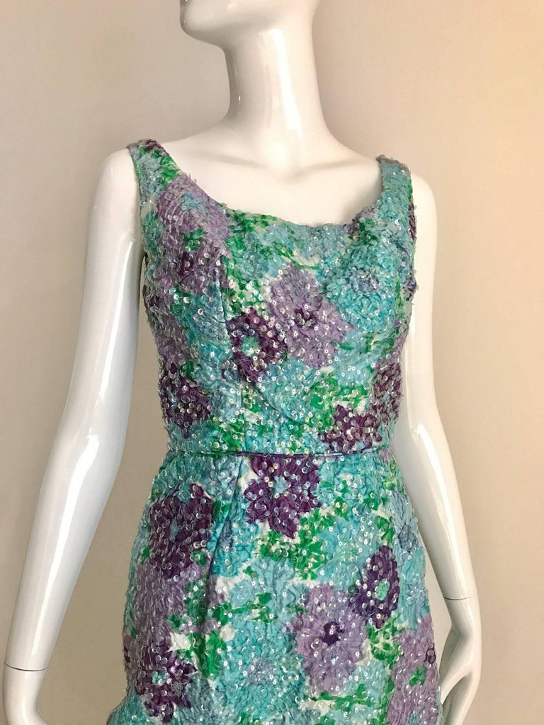 Late 1950s and early 1960s vintage cotton watercolor  floral print sheath dress. Iridescent clear sequins sewn all over the flower prints. Sleeveless Sheath wiggle style. The skirt has a back walking slit. Nylon zipper up the back. Bodice lined in