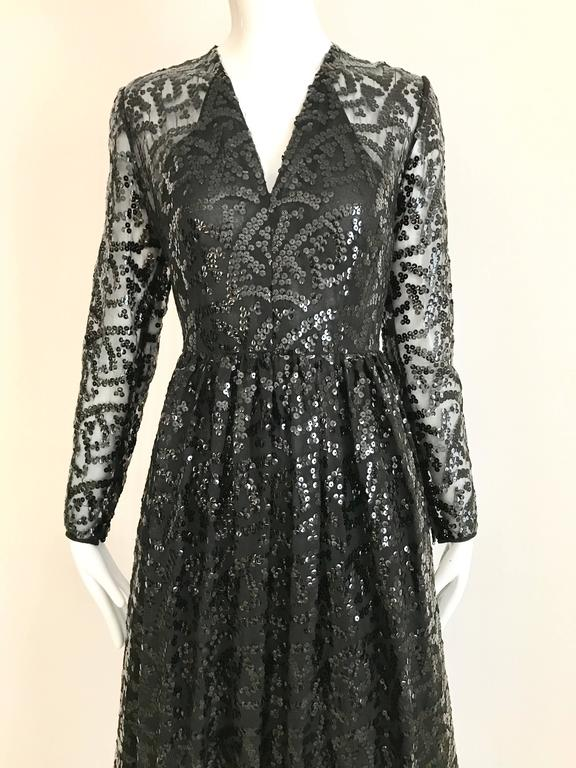 Late 1960s early 1970s Bill Blass black sequin V neck long sleeve dress with black ostrich feather hem. Semi Sheer Sleeves, and fitted in the waist. Perfect Black tie event. Size: 4  Bust: 34 inch  / Waist: 26 inch  / Hip: 40 inch/ Length: 51 inch/