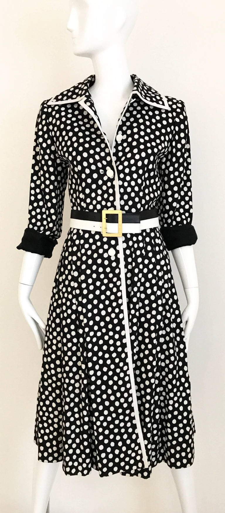 Vintage 1970s GIVENCHY Nouvelle Boutique black and White dot coat dress. 5 acrylic Button in the front and pleated skirt. Coat is made on linen and lined in silk. You can wear this as a dress. Coat has 2 side pockets. Coat is styled with Vintage
