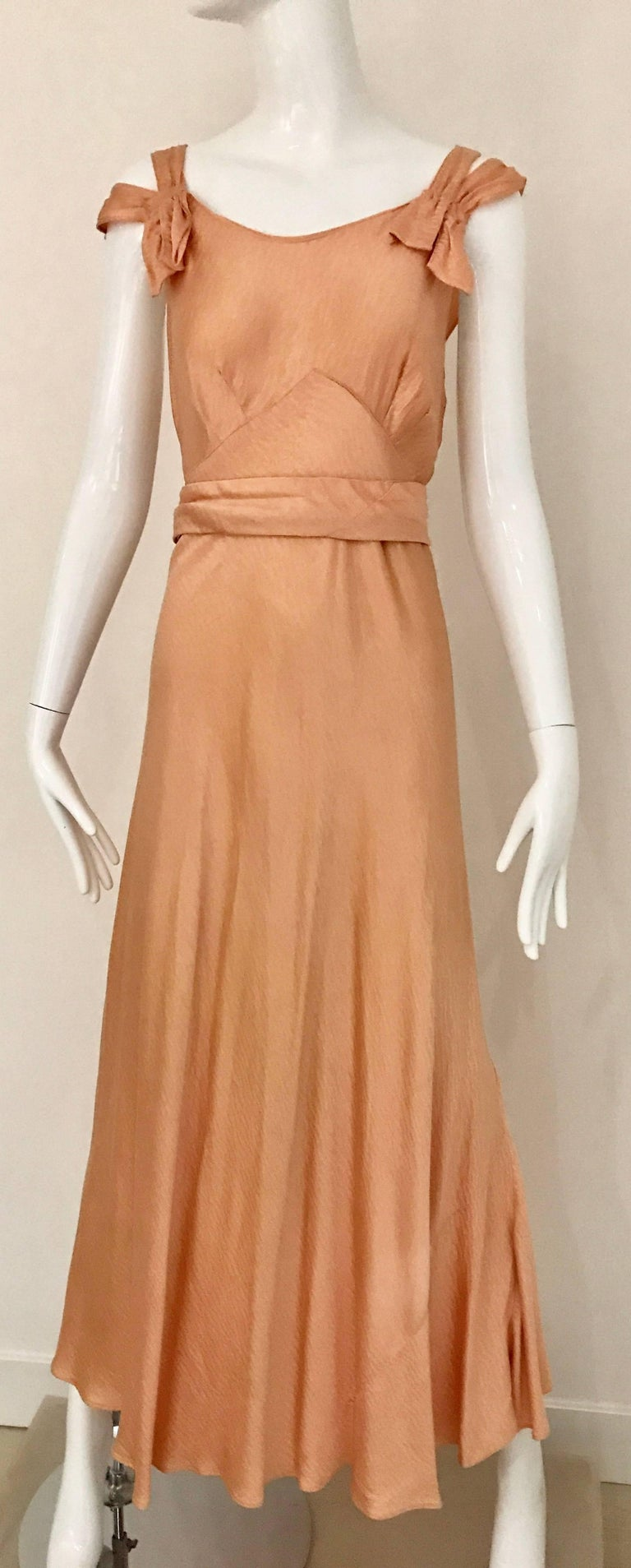 Beautiful 1930s peach silk spaghetti strap bias cut dress with trains at the back. Dress comes with capelet shawl.  Dress fit size 2/4 small Cape fit size 4/6 **small stains see image attached