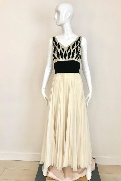 This vintage Phillip Hulitar 1950s, ivory silk chiffon and black velvet cocktail dress is the perfect party dress  or great for wedding.  Gown has intricate black velvet, ivory silk chiffon, pearl encrusted, leaf-motif bodice and its double-layer,