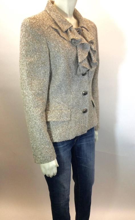 """Light Tan Tweed Exterior Ruffling Along Back Neckline and Front  Two Pockets, One on Either Side Five Buttons Along Front for Closure  100% Silk Interior  Sleeve Length; 24"""" Inches Long"""