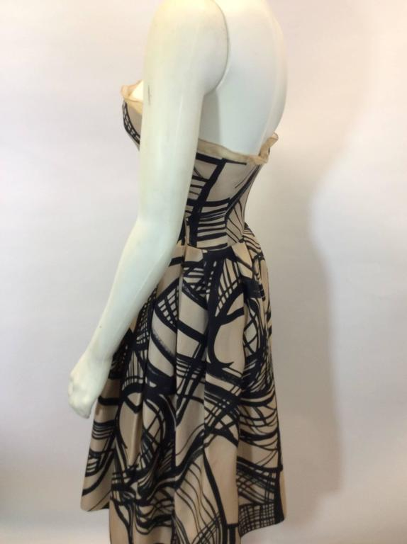 Cream and Black Printed Strapless Cocktail Dress Chiffon ruffle detail on bust Pleated skirt Side zipper closure with hook and eye bustier Padded bust Size 40 50% Cotton, 25% Polyurethane, 25% Nylon