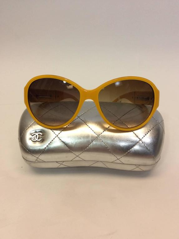 Yellow Framed Glasses with White Logo Inlay Brown ombre tinted lenses Chanel logo on side of glasses Chanel plate on inside of glasses Includes case