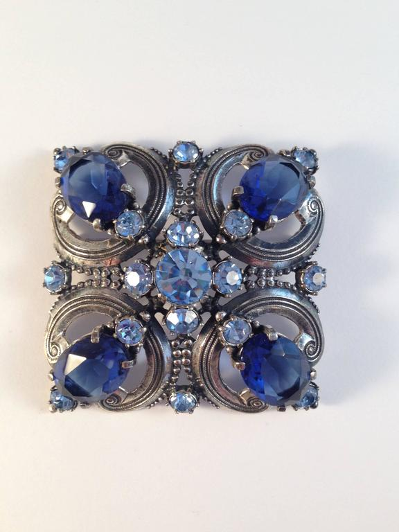 "This is a beautiful blue and silver-tone 1940s Elsa Schiaparelli brooch and clip-on earrings set. The brooch measures 2 3/8"" x 2 3/8"". It is silver-tone metal set with beautiful sapphire blue and light blue glass stones. It is in very good"
