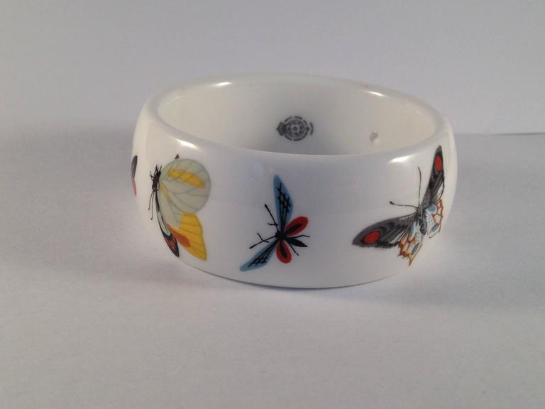 This is a bone china bracelet designed by Kenneth Jay Lane for the Royal Worchester Company. In 1976, Lane went to the Royal Worchester headquarters in England and chose several of their classic bone china patterns to fashion into necklaces and