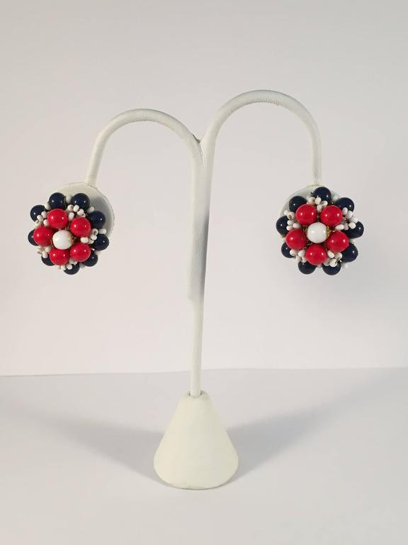 "Fun MOD 1960s Miriam Haskell red, white and blue beaded clip-on earrings. Classic filigree backs with brass wired elements. The earrings measure 1"" in diameter. They are clip earrings and have a clip-screw hardware mechanism that make for"