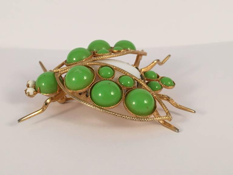 This is a green Kenneth Jay Lane bug brooch from the 1960s. The bug's body is made out of a white glass stone. The head and wings are made out of green resin beads. It measure 2 1/8