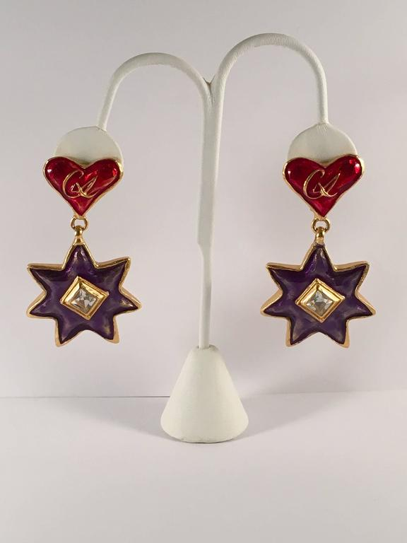 "This is a pair of Christian LaCroix clip-on dangle earrings from the 1990s. The clip portion features an enameled red heart with a gold ""CL"" in the center. The dangle portion features a blue enameled star with a shiny clear rhinestone in"