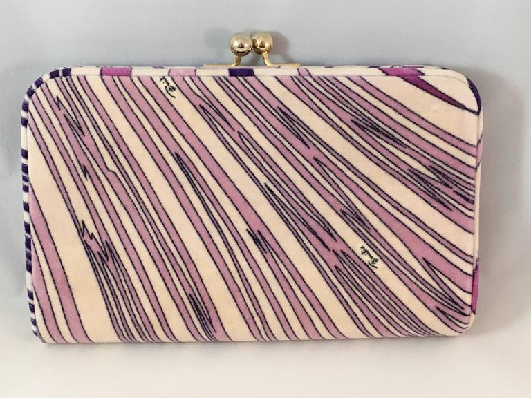 Gorgeous Pucci printed velvet clutch from the 1960's in excellent condition. All-over geometric print in shades of lilac and pink. The interior is lined in black satin. It closes with a snap closure at the top which is made up of two gold-toned