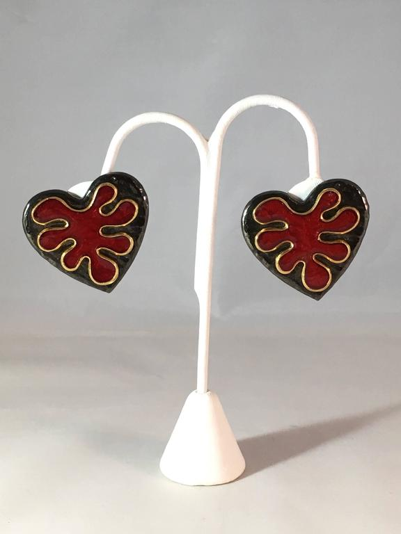 This is a pair of fabulous Yves Saint Laurent black and red heart clip-on earrings from the 1980s. The red portion in the center of the hearts look like Matisse cut-outs. The earrings are signed 'YSL' on the back of the clips and marked 'YSL' on the