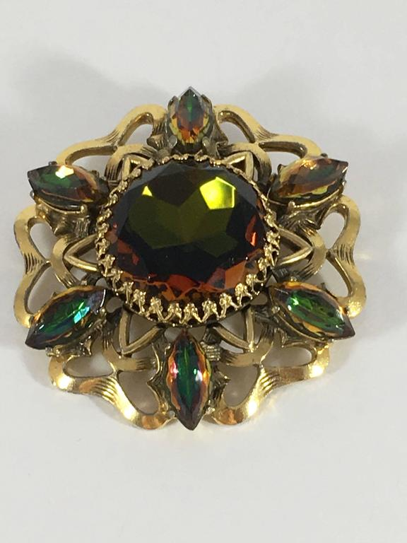 This is an Elsa Schiaparelli 1950s watermelon tourmaline brooch. It features a large watermelon tourmaline glass stone in the center surrounded by six smaller oval shaped tourmaline stones. The stones are set in a goldtoned base metal. The brooch