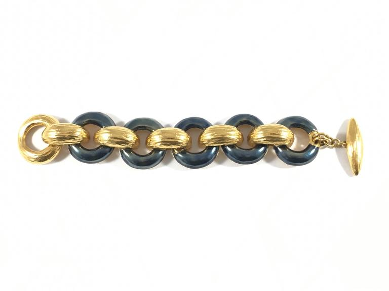 This beautiful 1980s bracelet is from Yves Saint Laurent's Rive Gauche line - the pret-a-porter line made especially for their Rive Gauche Boutiques. The bracelet is made up of heavy goldtone metal links interspersed with links covered in a