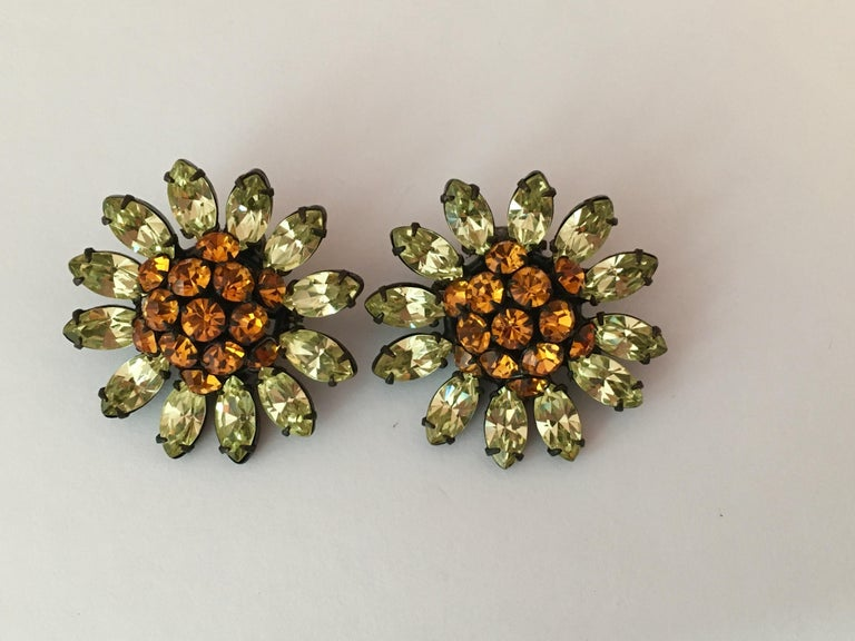 This is a pair of beautiful 1960s flower clip-on earrings by Schreiner New York. They have orange centers and yellowish green glass petals and are set in japanned metal. They measure 1 3/8 inches in diameter and are signed 'Schreiner' on the backs
