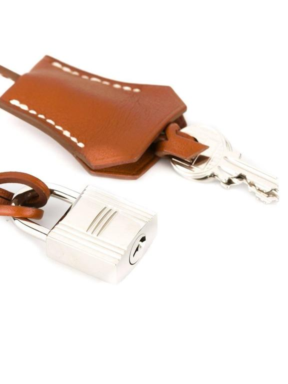 Hermès Vintage brown calf leather tag padlock featuring a silver-tone padlock and key.   Size : Width: 3.8 cm, Length: 26 cm  Excellent condition.