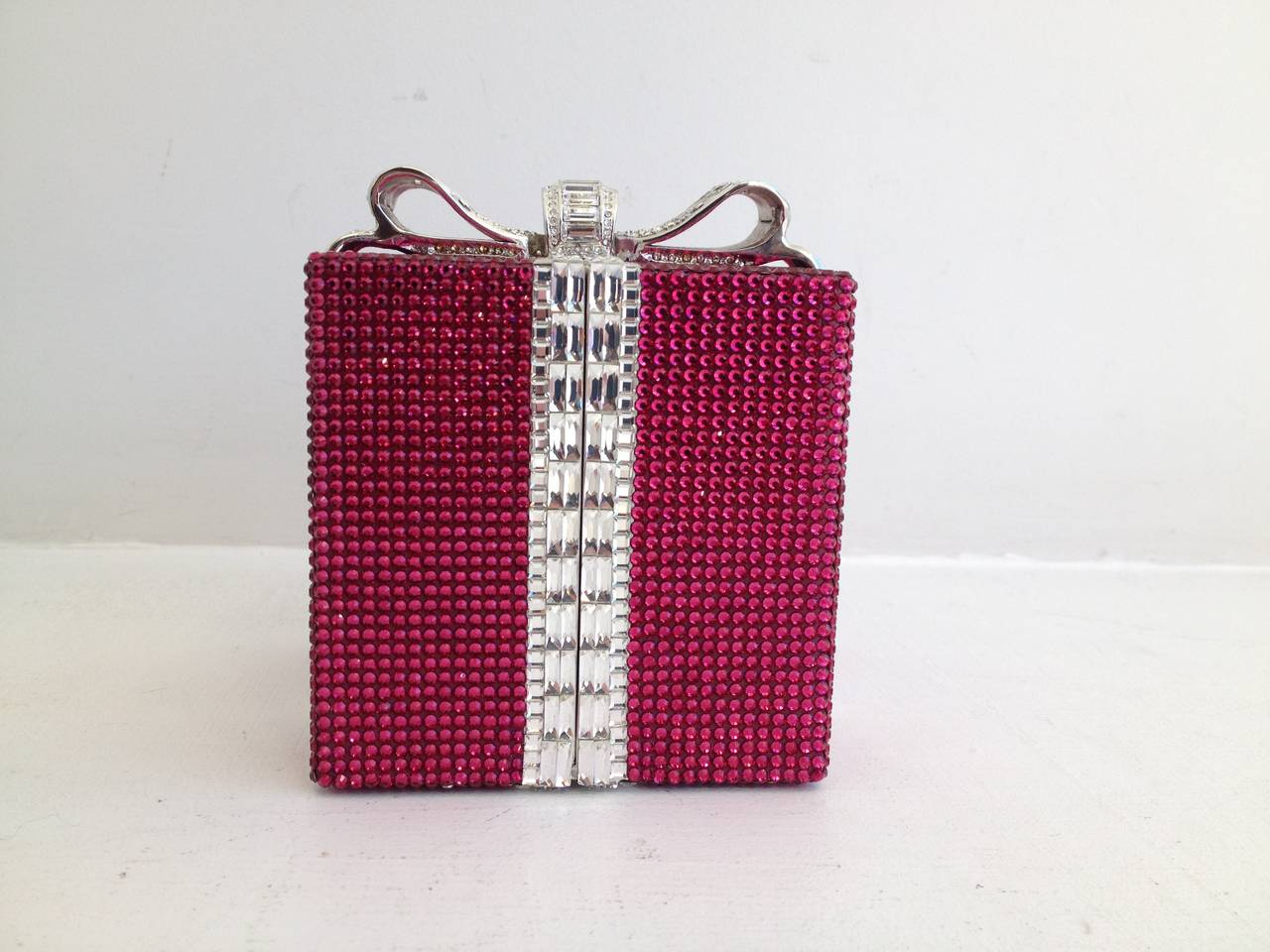 A present just for you! Wrapped in deep pink Swarovski crystals and tied with a silvery clear crystal bow, this little clutch is impeccable. The boxy silver interior fits a lipstick and your credit card, and the optional handle drops 8 inches to the