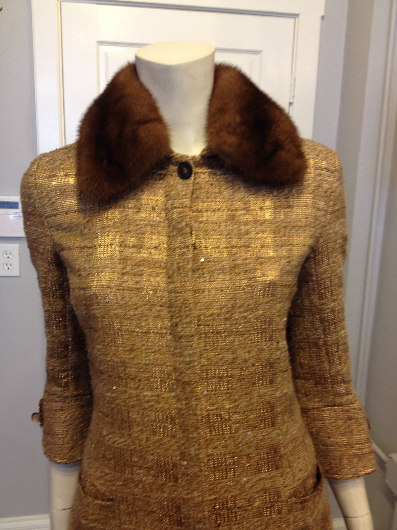 Regal and stately - this coat is sure to make an impact! The deep golden tone and the shimmering finish of the tweed are perfectly complemented by the mink collar and the clusters of amber-colored glass beads sewn onto each cuff. Perfect for the