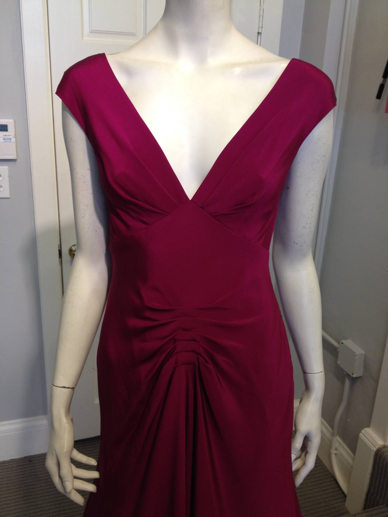 Red carpet ready! This piece is simply exquisite. The front is glamorous in a demure way, with a sharp and clean deep V-neck and a series of pleats to create a beautiful draping effect down the front of the skirt. The back, however, is so stunning -