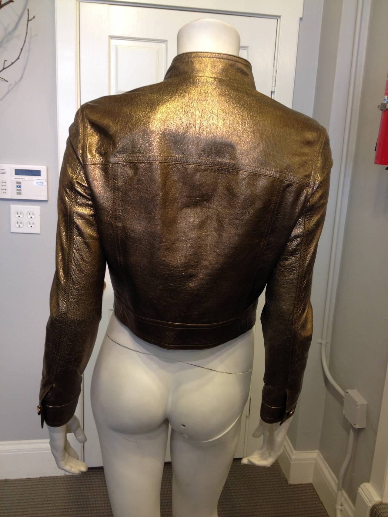 The ultra soft leather of this Celine jacket has a glossy bronze metallic finish, and the jean-jacket cut adds a cool and easy element for everyday. Wear this jacket with a hoodie and tight black jeans or over a cream satin slip dress - this piece