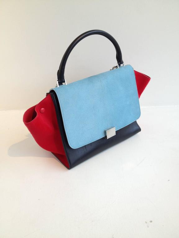 The beautifully saturated candy-bright pony hair in contrasting ruby red, sky blue and black adds such wonderful playfulness to this new Celine classic. This piece comes with both a short handle to carry the bag on your arm and a longer optional