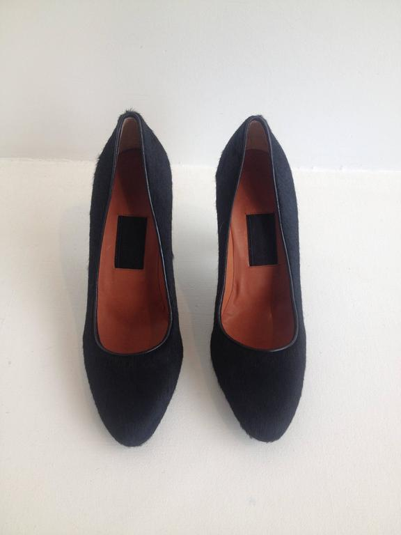 These wonderful shoes are sculptural but very wearable at the same time. It is very intriguing the way Lanvin contrasts colors and textures justopposing the black ponyhair body to the shiny smooth navy 3.75 inch heel. This is a shoe that can be worn