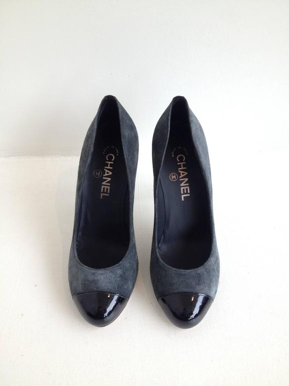 How gorgeous and modern. Lush deep smoky grey suede updates these classic pumps completely, while the glossy black patent cap toe adds polish - the contrast between the suede and patent textures is lovely. These have a four inch stiletto heel and a