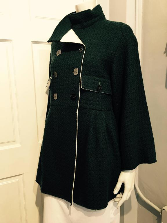 Chanel 3/4 length green tweed jacket in a houndstooth weave. The garment closes with a double row of square gunmetal color buttons with iconic CC and with two more smaller buttons on the flaps of two pockets at the waist. The skirt of the jacket has