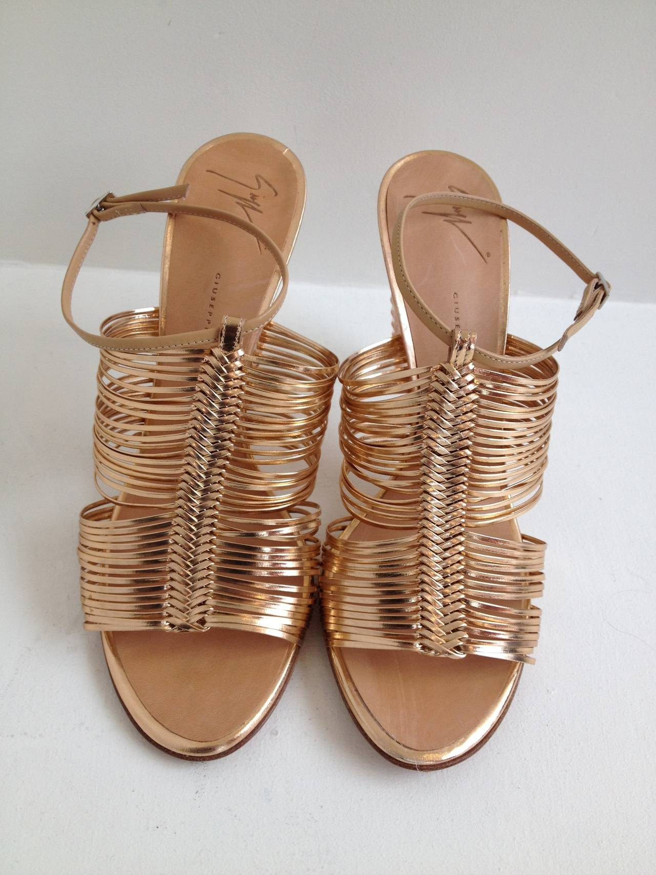 Giuseppe Zanotti is known for wild and bold footwear, and this shoe certainly proves it. The front of this sandal is a lattice of ultra thin rose gold metallic straps woven together into a fishtail-like braid. The 4.25 inch heel is cast to be