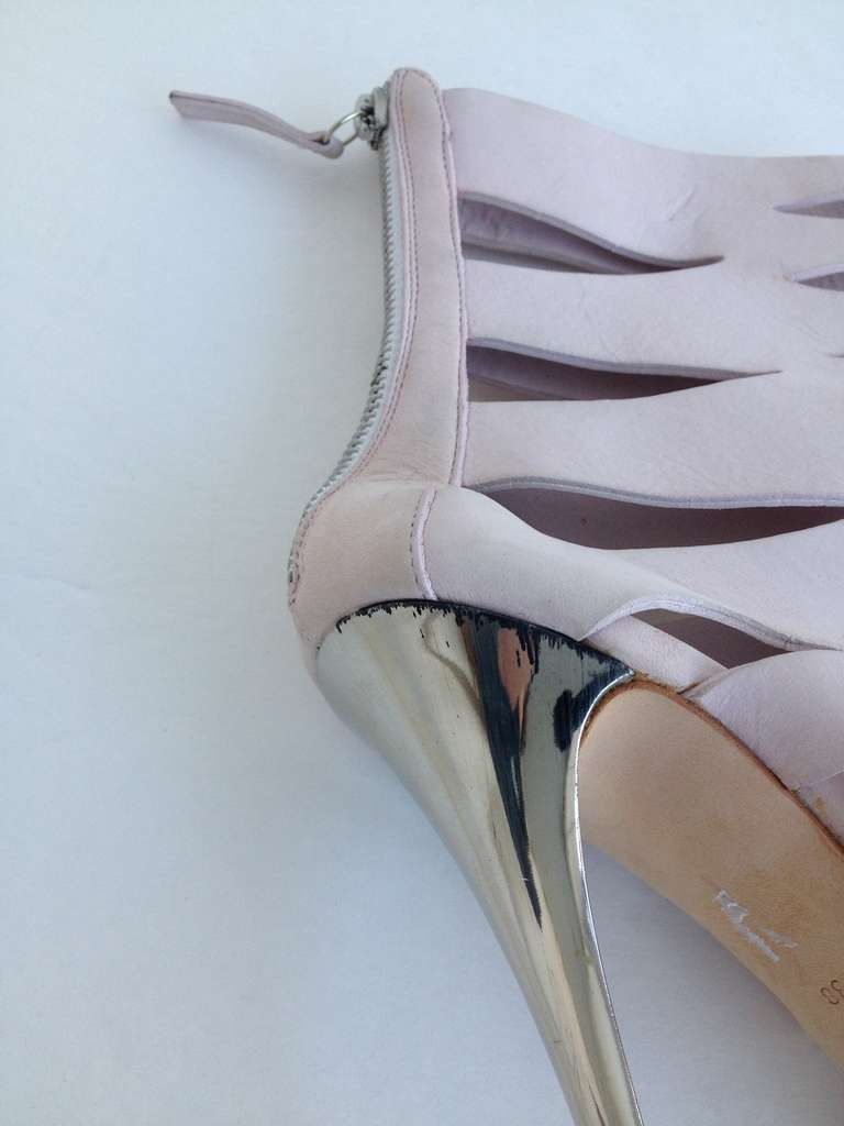 We love the contrast of this pretty, feminine pink leather and the sharp silver stiletto.  The small cutouts in the leather give the bootie a breezy, carefree style.  Perfect for toughening up a summer dress, or pairing with distressed, boyfriend